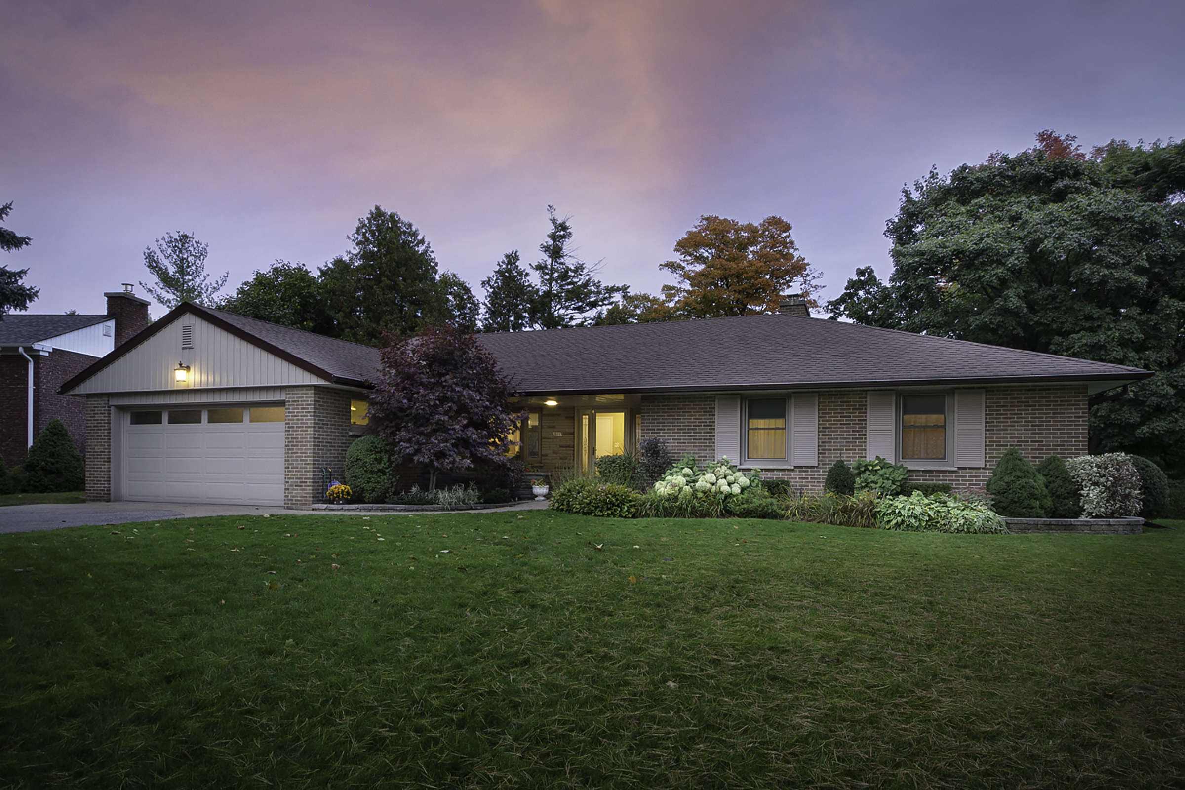 A photo of a large bungalow home taken at twilight