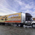 A tractor trailer featuring mobile advertising for Jensen Trailers
