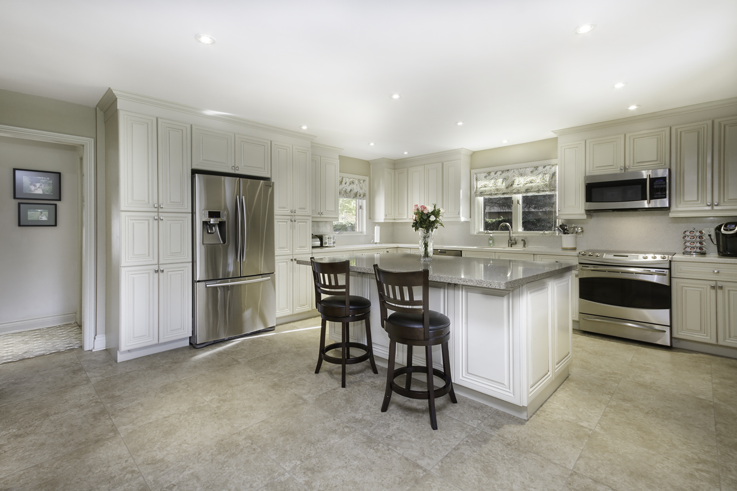 A large white kitchen with centre island