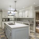 Renovated kitchen with white cabinets and center island